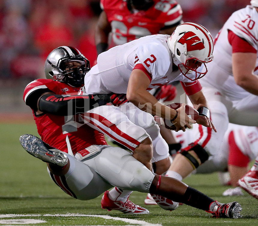 Ohio State Buckeyes linebacker Curtis Grant (14) brings down Wisconsin Badgers quarterback Joel Stave (2) during the second half of the game between Ohio State and Wisconsin at Ohio Stadium on Saturday, September 28, 2013. (Columbus Dispatch photo by Jonathan Quilter)