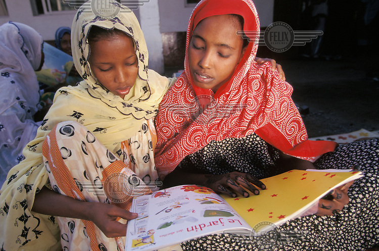 Girls reading a French language book at a youth centre. French and Arabic are the official languages of Djibouti.