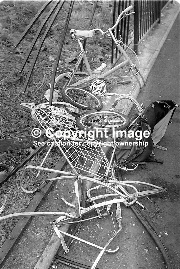 The mangled remains of a pram and a child's bike at the railings outside St John the Baptist school on Finaghy Road North, Belfast, where the three Maguire children died or were fatally injured on 10th August 1976. The incident occured when British soldiers fired on the car and fatally wounded the driver, Provisional IRA volunteer, Danny Lennon, 23 years, causing the vehicle to go out of control and mount the footpath. Joanne Maguire, 8 years, and her brother, Andrew Maguire, 6 weeks, were killed instantly. John Maguire, 2 years, died the following day. Their mother, Anne Maguire, never fully recovered and took her own life on 21st January 1980. The children's deaths triggered the formation of the Peace People movement. 197608100362. <br />