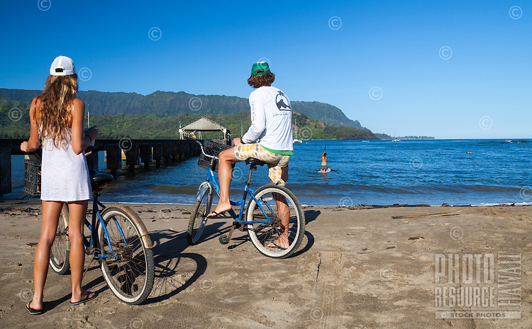 A couple with bikes watch a standup paddler make her way out to Hanalei Bay near the pier by Hanalei Beach, Kaua'i.