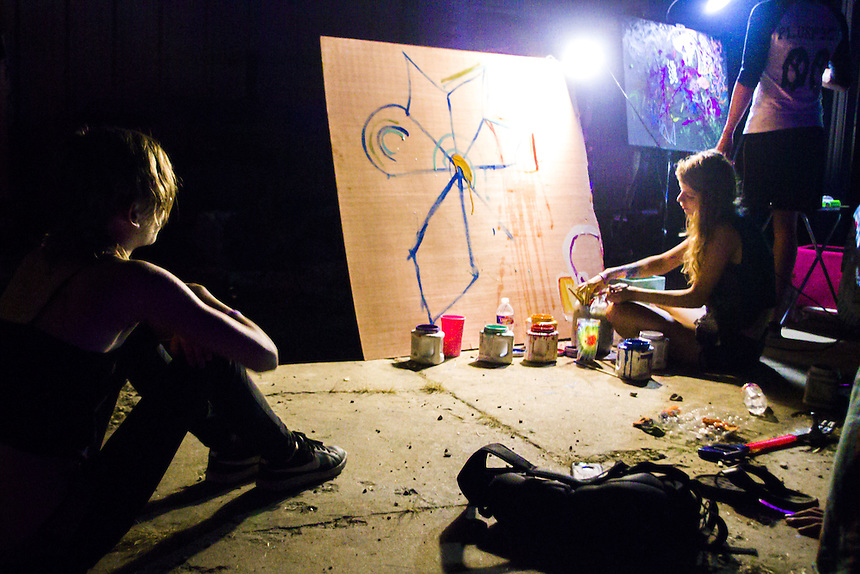 A woman paints an art piece as festival goers watch nearby.