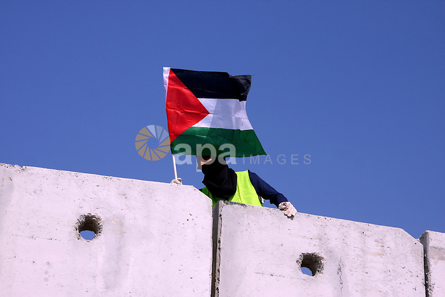 "foreign activist as he stands on top of Israel's controversial separation barrier during a protest in the Qalandia refugee camp, near the West Bank city of Ramallah, on November 9, 2009 to mark the 20th anniversary of the fall of the Berlin Wall in Germany. Palestinians are using the anniversary of the end of the Berlin wall to press their campaign against Israel's ""wall"", mostly a razor-wire fence interspersed with concrete barricades which Israel began building around the West Bank in 2002. The Jewish state has come under international censure for the barrier's de facto annexation of occupied West Bank land.. Photo by Issam Rimawi"