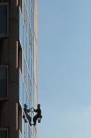 Rope access technician cleans windows on a building near Zoshigaya, Tokyo, Japan. Friday January 15th 2016