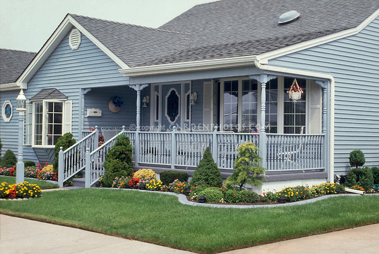 Curb appeal blue house, lawn, foundation plantings, flowers, entrance garden, front entry with lawn grass, front porch, curving garden borders beds