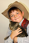 A cowboy holding a kitten