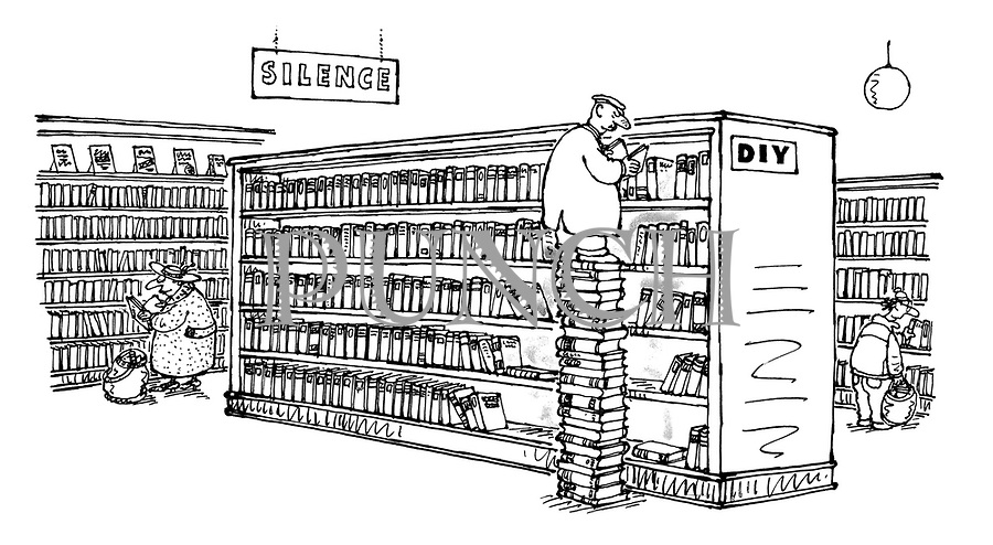 (Man in a library standing on a pile of books to look at books on the top shelf of the DIY section)