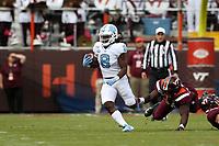 BLACKSBURG, VA - OCTOBER 19: Michael Carter #8 of the University of North Carolina avoids a tackle by Norell Pollard #96 of Virginia Tech during a game between North Carolina and Virginia Tech at Lane Stadium on October 19, 2019 in Blacksburg, Virginia.