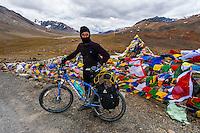 A bicyclist stops at the summit of 16,000 foot Bara-lacha Pass, Leh-Manali Highway, Himachal Pradesh, India.