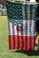 AJ Alexander - A Protester carries an American Flag with the Mexican Flag stiched over it about 250 SB1070 Opponents Marched to Arizona State Capitol on the one year anniversary of the SB1070 signing. On Saturday, April 23, 2011..Photo by AJ Alexander.www.ajaimges.photoshelter.com