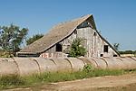 Wooden barn with hay rolls in rural Nebraska.