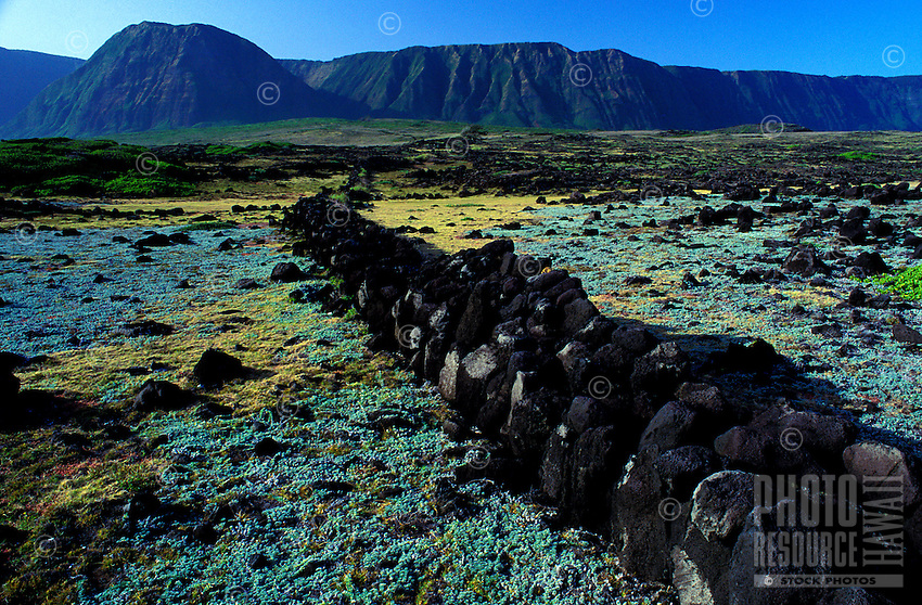 Ancient stone wall, used historically as a land division marker, with mountains in the background, Kalaupapa peninsula