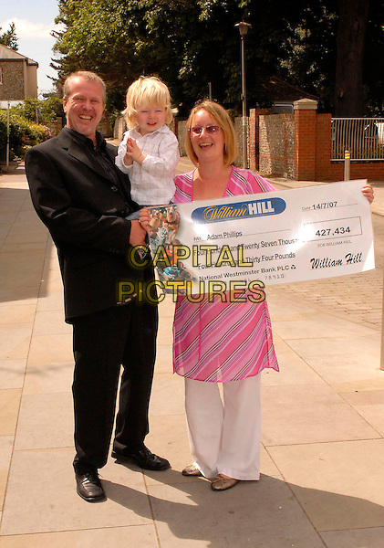 ADAM PHILLIPS (Aged 40) , son Charlie (Aged 2) & wife Sue (Aged 38) .Adam and Sue from Littlehampton, Sussex, have won £427,434 from William Hill bookmakers, after placing a £2.00 bet..Chichester, West Sussex,17th July 2007..full length cheque celebrating win gambling betting bookies.CAP/FIN.©Steve Finn/Capital Pictures.