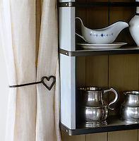 Pale linen curtains are held back with a simple heart-shaped metal band beside an open shelf in this kitchen