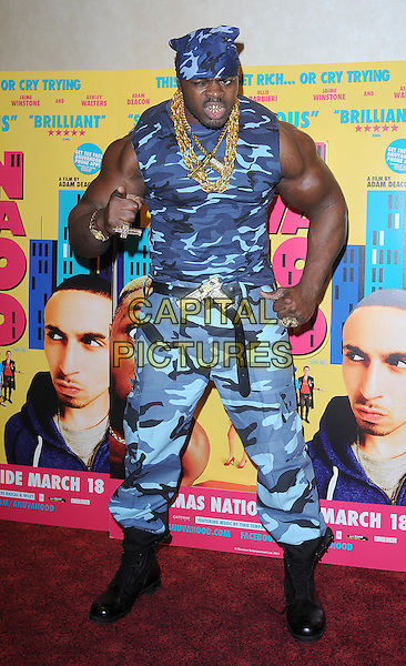 "TINY IRON.attending the UK Premiere of ""Anuvahood"", Empire cinema, Leicester Square, London, England, UK, .15th March 2011.full length body builder strong arms pose biceps muscles blue camouflage  belt black boots  gold necklace  vest trousers hand finger pointing bandana .CAP/BEL.©Tom Belcher/Capital Pictures."