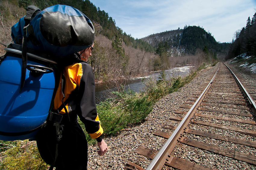 A canoeist portages around a rapids along railroad tracks on the Agawa River of Ontario Canada.