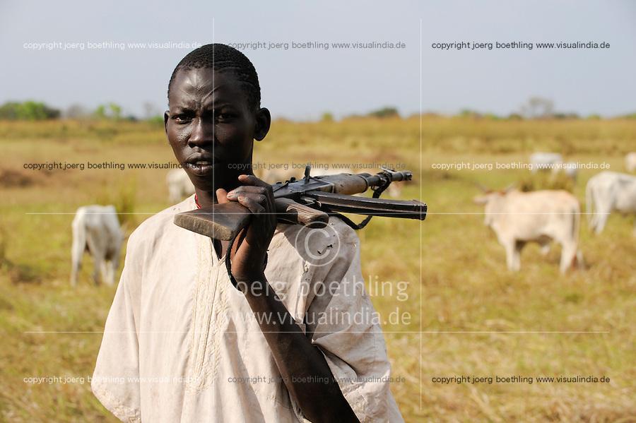 SOUTH SUDAN, Rumbek, young Dinka man protect the Zebu cattle of his family with AK-47 rifle against Nuer cattle raider / SUED SUDAN Rumbek , Matur ein 18 jaehriger Dinka Hirte schuetzt Zeburinder vor Viehdiebstaehlen durch Nuer mit seinem Kalaschnikov Maschinengewehr