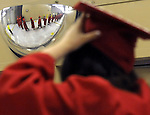 A Manchester High graduate adjusts her cap using  a security mirror on the wall as the march starts from behind the scenes at the Convention Center, at the beginning of their graduation ceremony, Thursday, June 20, 2013, in Hartford. (Jim Michaud / Journal Inquirer)