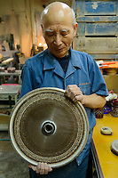Edokiriko artisan Ryuzo Mita holds a large diamond grinding wheel. Shimizu Glass, Tokyo, Japan, January 14, 2015. Edokiriko is a style of cut glass that dates back to 1834 and is similar to British cut glass. It makes use coloured glass and highly-intricate Japanese motifs.