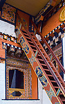 Traditionally decorative stair lead to a curious, small, square door above an ornately decorated window in the courtyard of the Chimi Lakhang Temple in Bhutan. The windows and stairs are painted a brick red and decorated in blues and golds enhanced by the surrounding white walls.