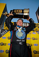 Nov 17, 2019; Pomona, CA, USA; NHRA funny car driver Robert Hight celebrates with he championship trophy after clinching the 2019 funny car world championship during the Auto Club Finals at Auto Club Raceway at Pomona. Mandatory Credit: Mark J. Rebilas-USA TODAY Sports