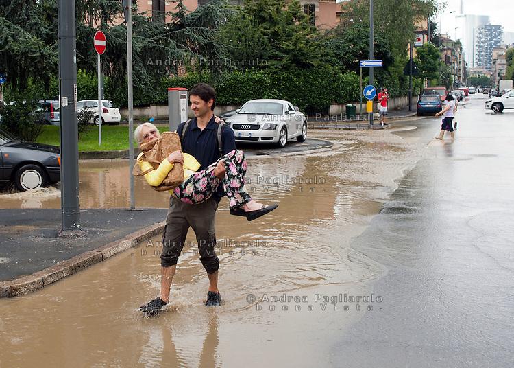 Milano,  viale Sarca.<br /> Esondazione fiume Seveso.<br /> Giovane aiuta anziana signora ad attraversare la strada.<br /> Milan, flooding of the river Seveso.