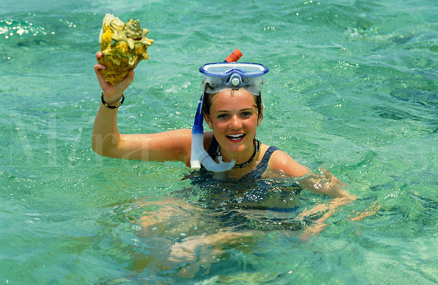 Teenage girl snorkeling in the Caribbean, with conch shell..