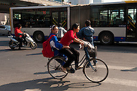 Daytime landscape view of two women riding a bike at the intersection of Chao Yang Bei Lu and Dong San Huan Zhong Lu in Cháoyáng Q? in Beijing.  © LAN