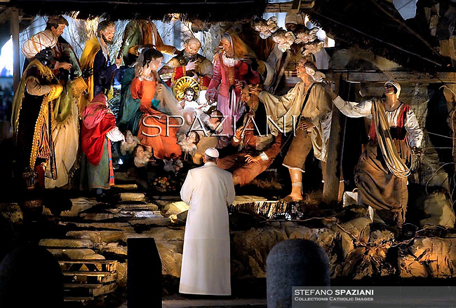 Pope Francis  prays in front of a Nativity scene in St Peter's square at the Vatican on December 31, 2013.