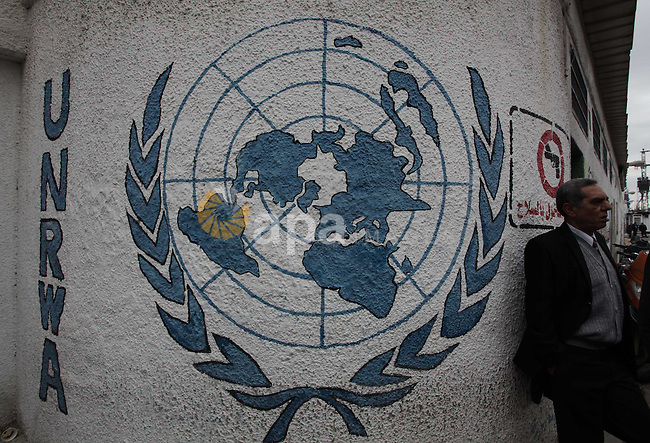 Palestinians hold banners during a protest against the UNRWA decision reduce salaries in front of the headquarters United Nations Relief and Works Agency (UNRWA) in Gaza city, on Dec. 10, 2013. Photo by Ashraf Amra