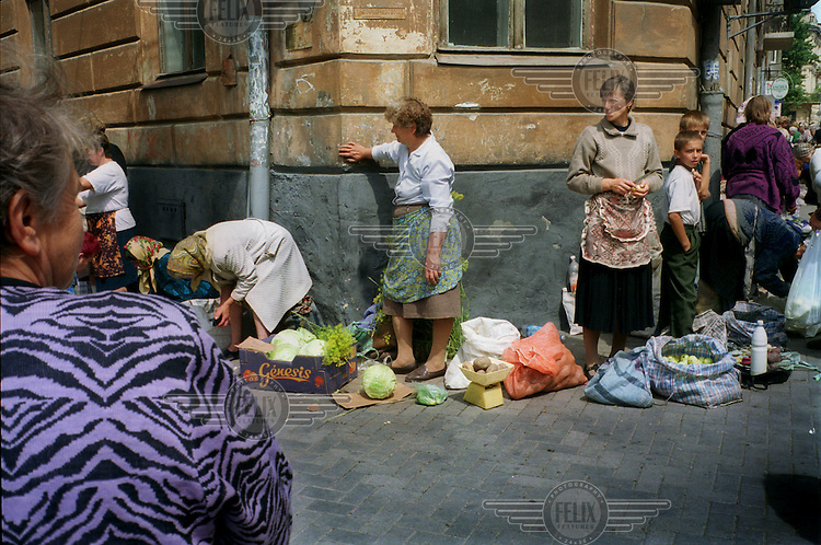 Poor women and children sell homegrown vegetables, milk and trinkets on a street in Lviv.