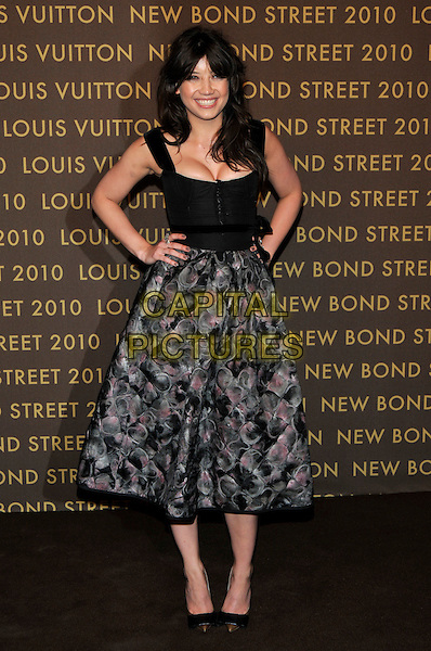 DAISY LOWE .attends the launch of the Louis Vuitton Bond Street Maison in London, England, UK, May 25th, 2010..full length black sleeveless dress hands on hips grey gray print skirt hands on hip cleavage smiling bodice buttons sash waist belt pink gold toe cap two tone shoes  .CAP/PL.©Phil Loftus/Capital Pictures.