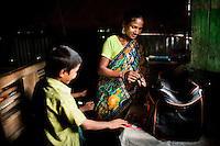 Shahida Begum, 35, organises her products with her son, Shakil Alom (7), in her hut in Palashbari Villlage, Taragonj, Rangpur, Bangladesh on 18th September 2011, after a regular day of work as a saleswoman earning 3500 - 5000 Bangladeshi Taka per month. She is one of many rural Bangladeshi women trained by NGO CARE Bangladesh as part of their project on empowering women in this traditionally patriarchal society. Named 'Aparajitas', which means 'women who never accept defeat', these women are trained to sell products in their villages and others around them from door-to-door, bringing global products from brands such as BATA, Unilever and GDFL to the most remote of villages, and bringing social and financial empowerment to themselves.  Photo by Suzanne Lee for The Guardian