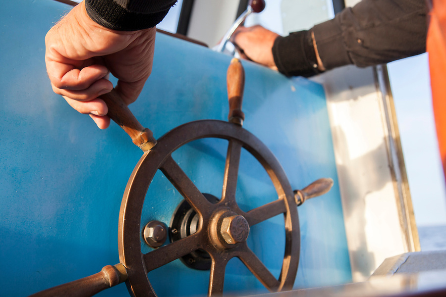 A fisherman's hands on the boat's wheel.