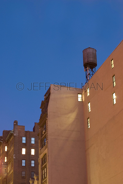 AVAILABLE FROM JEFF AS A FINE ART PRINT.<br /> <br /> AVAILABLE FROM PLAINPICTURE FOR COMMERCIAL AND EDITORIAL LICENSING.  Please go to www.plainpicture.com and search for image # p5690102.<br /> <br /> Building with Illuminated Windows and Water Tower on Roof at Dusk, Union Square, New York City, New York State, USA