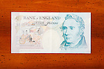 Five pound British currency note on table showing George Stephenson
