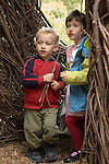 Sausalito CA Siblings age two and four exploring willow structure at Bay Area Discovery Museum  MR