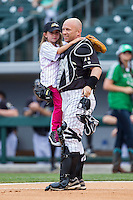 Isabella Elmore (left) gets a hug from her father, Phillip Elmore, Gunner's Mate 1st Class in the U.S. Navy, as he surprised her by dressing as a catcher to catch her ceremonial first pitch prior to the International League baseball game between the Buffalo Bison and the Charlotte Knights at BB&T Ballpark on May 9, 2014 in Charlotte, North Carolina.  Phillip Elmore is currently stationed in Germany, and he planned the surprise trip home to coincide with Isabella's graduation from her communion class.  (Brian Westerholt/Four Seam Images)