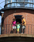 Aquinnah, MA - August 27, 2009 -- Malia, 11, and Sasha, 8, Obama, with a Secret Service agent, peer from Gay Head Lighthouse, first used in 1799, in Aquinnah on Martha's Vineyard, Mass. Thursday, August 27, 2009. The Obama's visited the lighthouse with President Obama's brother-in-law Konrad Ng and Obama's friend Eric Whitaker and his family after a bike ride in Aquinnah. .Credit: Vincent DeWitt - Pool via CNP