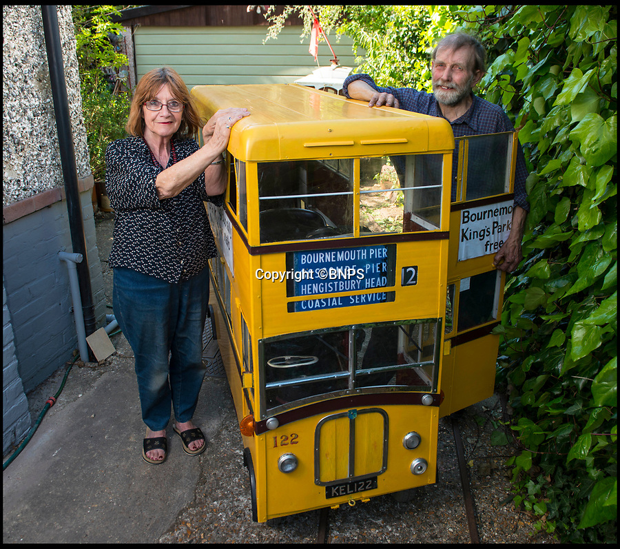BNPS.co.uk (01202 558833)<br /> Pic: TomWren/BNPS<br /> <br /> Keith Burbidge and his wife Carol.<br /> <br /> Dinky decker...<br /> <br /> A retired bus driver has taken his passion for buses to the next level - by transforming a broken mobility scooter into a quirky mini yellow bus.<br /> <br /> Keith Burbidge, 75, retired as a coach driver last year but missed the mode of public transport so much he decided to make his own miniature version.<br /> <br /> The father-of-two spent just £40 and six months turning a broken scooter he picked up at auction into a working scale-model of a Yellow Bus, the company that operates in his hometown of Bournemouth, Dorset.<br /> <br /> The one-of-a-kind motor is 4ft tall and 6ft long and can only travel at speeds of about 5mph.