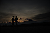 Walkers are silhouetted against the setting sun along the bay in Puerto Princesa, Palawan in the Philippines. <br /> Photo: Sanjit Das/Panos for Greenpeace