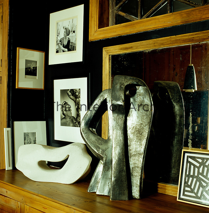 A collection of black and white photographs and sculpture is displayed in the kitchen