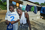 Ceneprise Etienne laughs with her husband Antilio Tilsaint in front of their family's new home in Djondgon, a village near Jean-Rabel in northwestern Haiti. The family's previous house was destroyed during Hurricane Matthew in 2016, and Church World Service, a member of the ACT Alliance, helped the family build their sturdy new home.