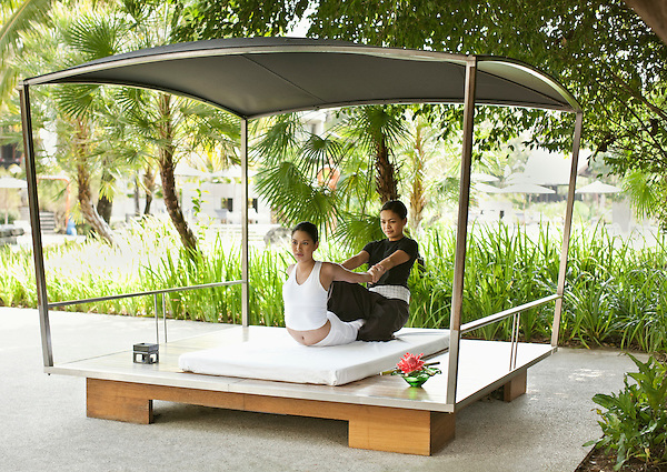 A woman receives a Thai Massage in an outdoor cabana by the main pool. The Thai Massage is a 60- to 90-minute spa treatment offered by IN-DI-GO Spa, the resort's on-site spa facility, Indigo Pearl Resort, Phuket, Thailand.