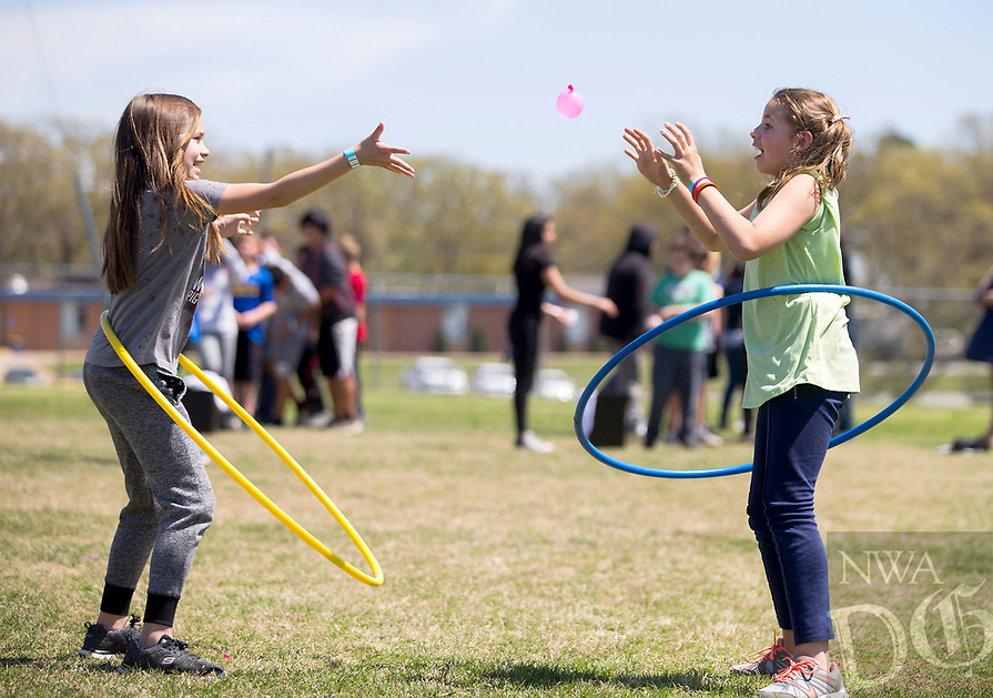 NWA Democrat-Gazette/JASON IVESTER<br /> Hailey Mejia (left) and Annabelle Bell, both Decatur fifth-graders, toss a water balloon while hula-hooping Wednesday, April 12, 2017, on the Decatur football field. A group of Decatur eighth-graders organized the event, Revolution 2021, for Decatur Middle School students.