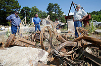 "NWA Democrat-Gazette/DAVID GOTTSCHALK Rob Mullins (from left), Public Works Manager with the city of Eureka Springs, Director Dwayne Allen, and Mayor Robert ""Butch"" Berry, review Friday, June 29, 2018, the remains of two wooden spoked vehicles at the city Public Works yard in Eureka Springs. The two vehicles and other objects of antiquity, including newspaper pages, were discovered during an excavation of a site at Main and Flint Streets in Eureka Springs. The excavation is taking place during storm water drainage repairs."
