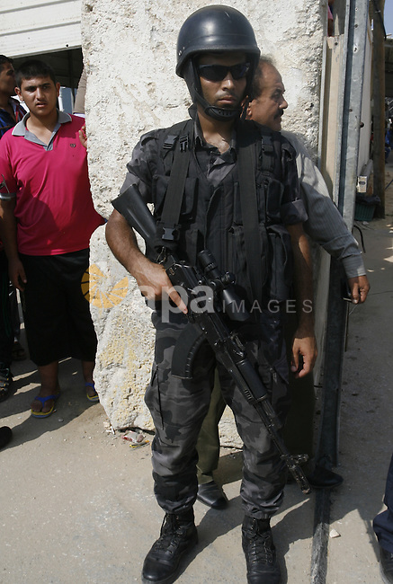 A Palestinian security officer stands guard as Prime Minister Rami Hamdallah visits Beit Hanoun in the northern Gaza Strip on October 9, 2014. The Palestinian unity government which took the oath of office in June under technocrat prime minister Rami Hamdallah arrived to Gaza Strip on Thursday to convene the first fully meeting. Hamdallah said that the unity government will rebuild the bombed-out Gaza Strip following a seven-week Israeli offensive. Photo by Abed Rahim Khatib
