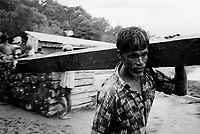 Rohingya man unloads timber from a boat at a port near Teknaf. (2008)