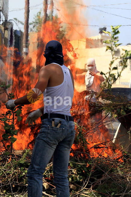 Palestinian protesters set fire during clashes with Israeli police in Jabal al-Mukaber neighborhood, southern Jerusalem, on October 13, 2015. A wave of stabbings that hit Israel, Jerusalem and the West Bank this month along with violent protests in annexed east Jerusalem and the occupied West Bank, has led to warnings that a full-scale Palestinian uprising, or third intifada, could erupt. The unrest has also spread to the Gaza Strip, with clashes along the border in recent days leaving nine Palestinians dead from Israeli fire. Photo by Mahfouz Abu Turk