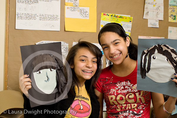 Education Middle School grade 8 art activity cut paper self portraits two girls holding up art work and posing horizontal