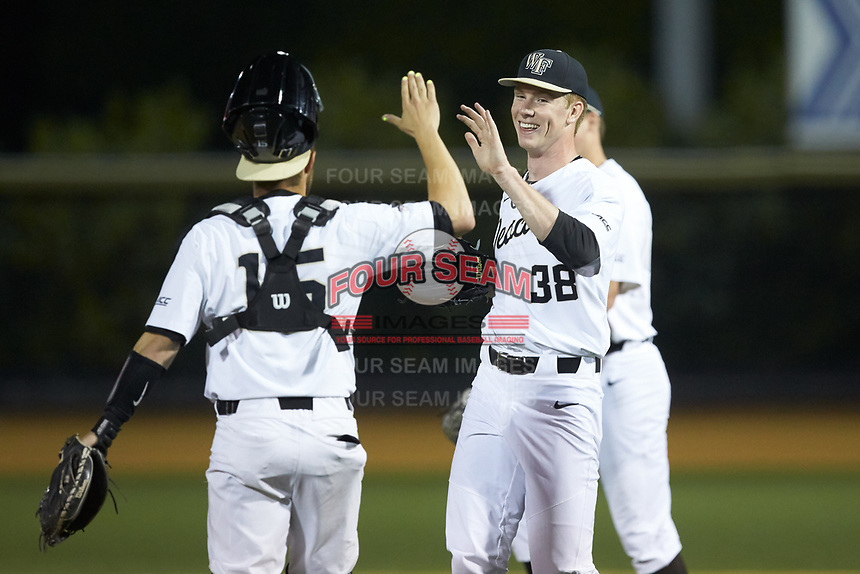 Wake Forest Demon Deacons relief pitcher William Fleming (38) high fives catcher Logan Harvey (15) after closing out the win over the North Carolina State Wolfpack at David F. Couch Ballpark on April 18, 2019 in  Winston-Salem, North Carolina. The Demon Deacons defeated the Wolfpack 7-3. (Brian Westerholt/Four Seam Images)
